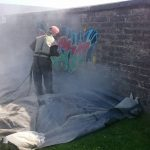 man sandblasting graffitied wall